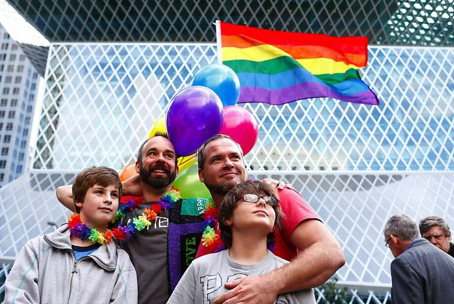 Shawn Kelly, left center, with his son, Caspian Kelly, 12, left, celebrate at the old Federal Courthouse in Seattle with his partner, Chris McDaniel, center right, and his son, Max McDaniel, 12, on Wednesday, June 26, 2013, in Seattle, The two, who are not married, were there with others in celebration of the striking down of the Defense of Marriage Act earlier today by the U.S. Supreme Court. (AP Photo/The Seattle Times, John Lok)  Photo: John Lok, Associated Press
