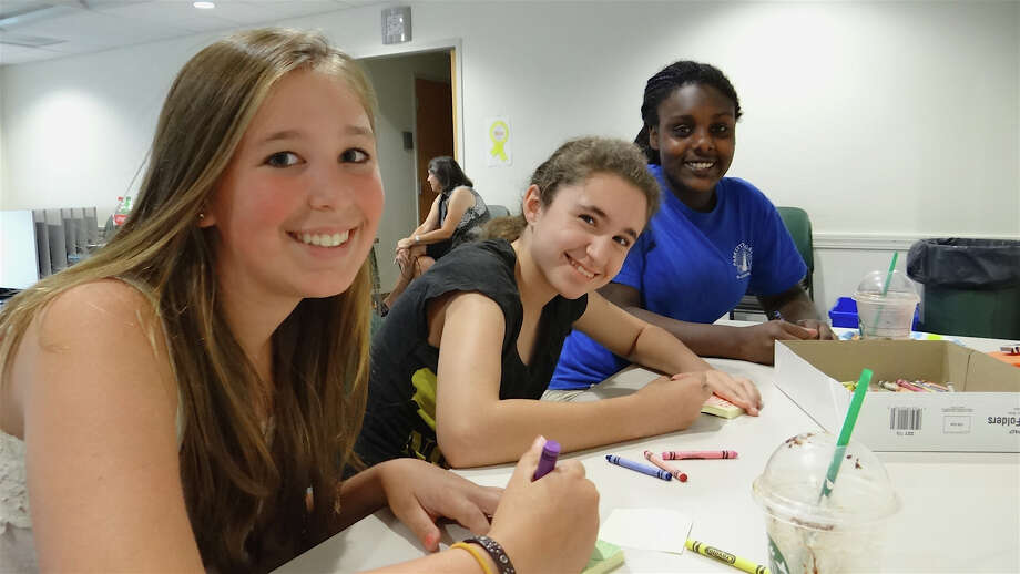 Fairfielders Isabella Huban, 13; Anna Ciraulo, 12, and Maya Vetrosky, 13, draw designs for a Post-It Gallery at Fairfield Library's Teen Summer Challenge kickoff on June 26. Photo: Mike Lauterborn / Fairfield Citizen