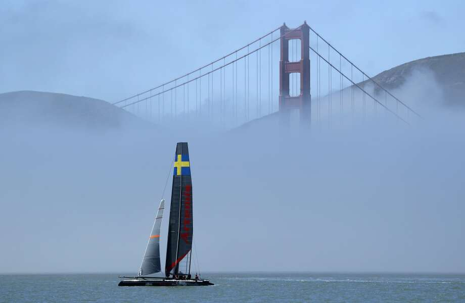 An AC45 catamaran from Artemis Racing of Sweden makes its way past fog and the Golden Gate Bridge during training for the America's Cup on Wednesday, June 26, 2013, in San Francisco. Opening ceremonies for the sailing event are on July 4. Artemis is training on its smaller AC45 boats until its larger AC72 is ready in late July. Photo: Eric Risberg, Associated Press