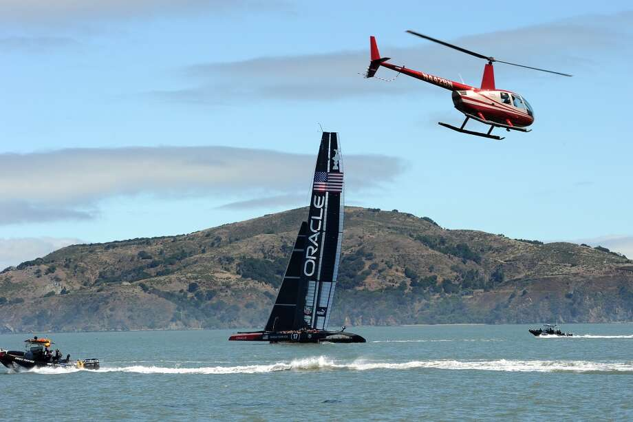 Support boats and a helicopter shadow the Oracle Team USA's AC-72 catamarans in San Francisco Bay Wednesday June 26th, 2013, as crews ramped up their training for the upcoming America's Cup finals in September. Photo: Michael Short, Special To The Chronicle