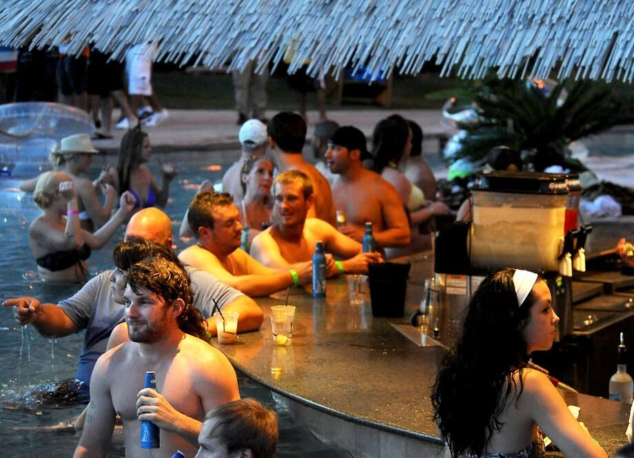 Partiers belly up to the tiki themed pool bar during the Liquid Society party at L'Auberge in Lake Charles, Thursday, July 26, 2012. Tammy McKinley/The Enterprise