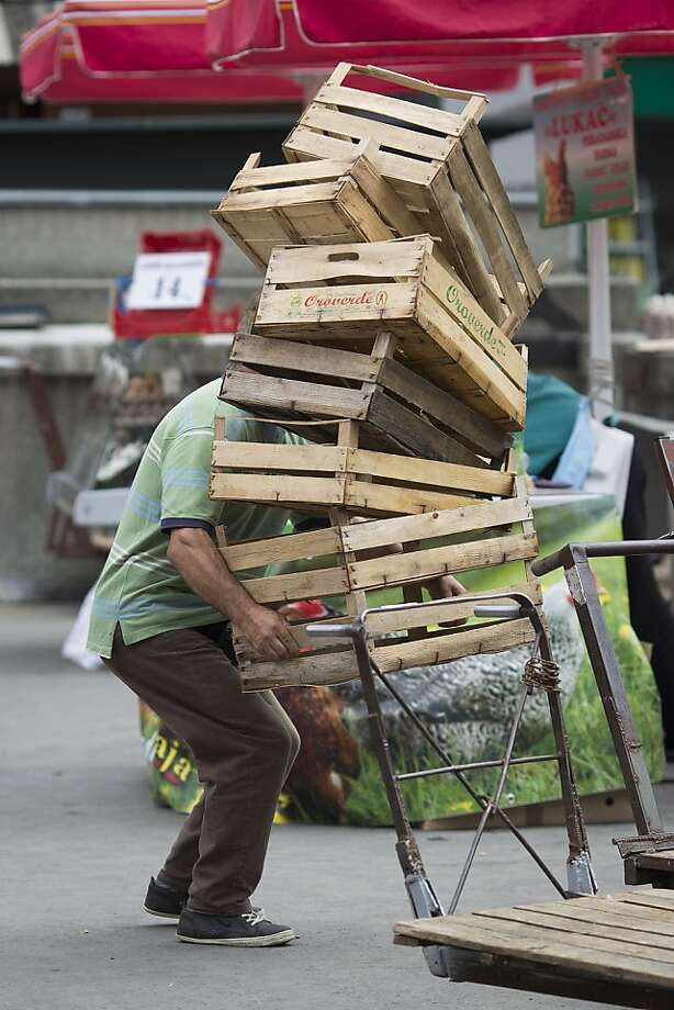 Balancing act:A worker tries to keep a stack of crates from toppling in the Dolac Market in Zagreb, Croatia. Photo: Simon Dawson, Bloomberg