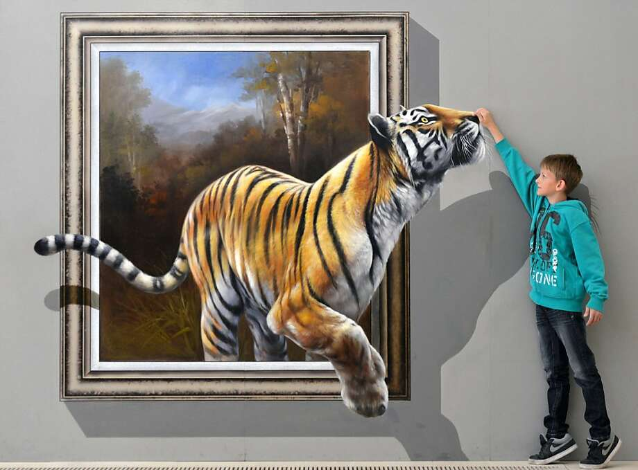 Dustin tickles a tigerlunging from a 3-D painting by a Chinese-Korean artist group at the exhibition Du bist die Kunst! (You are the Art!) at Augustusburg Palace in Augustusburg, Germany. Visitors are invited to take pictures of themselves interacting with the art and share the results on social networks. Photo: Hendrik Schmidt, AFP/Getty Images