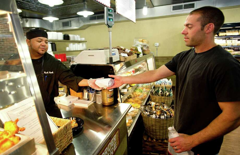 Chef Oscar Hernandez hands a sandwich to Barry Denison at Mish Mosh deli and market in Stamford, Conn., on Thursday, June 27, 2013. Photo: Lindsay Perry / Stamford Advocate