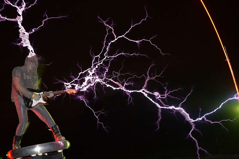 Concert conductor:With the help of a Tesla Coil, Wang Hongbin of the band Lightningfan shoots bolts from his guitar outside Fuzhou in China's Fujian province. The Tesla   Coil, invented by Nikola Tesla in 1891, is a transformer that produces vast amounts of voltage at high frequencies, creating long bolts of electricity similar to lightning. Lightningfan's members wear ferric alloy metal suits while they play guitars, violins and drums. Photo: Peter Parks, AFP/Getty Images