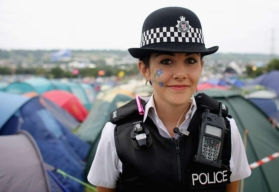 Face painted for the festivities,Special Constable Sandie Davies keeps the peace at the Glastonbury Festival at Worthy Farm in Pilton, England. The massive music gathering - with bands this year including Arctic Monkeys, Mumford and Sons, and the Rolling Stones - is expected to attract more than 175,000 people over five days. Photo: Matt Cardy, Getty Images