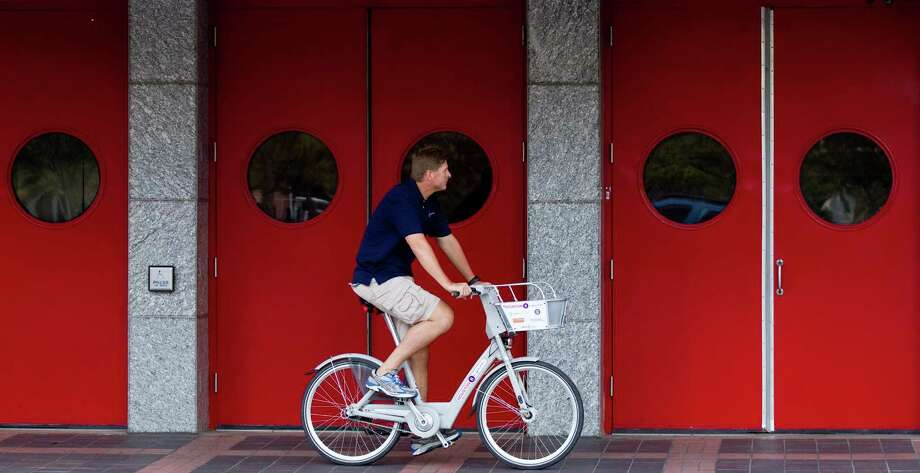 Will Rub, director of Houston Bike Share, rides downtown on one of the B-cycle rental bicycles. Photo: Brett Coomer, Houston Chronicle / © 2012 Houston Chronicle