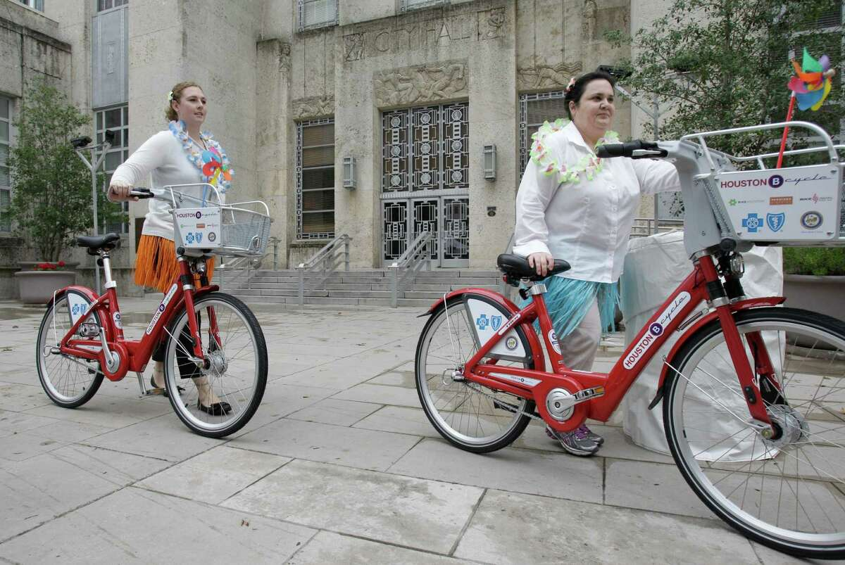 Jackie Posenecker, left, and Jackie Lambert, right, employees with Central Houston arrive outside City Hall Wednesday, April 3, 2013, in Houston. B-Cycle riders came to the City Hall Farmers Market where Mayor Annise Parker held a news conference about the Houston bike share program expansion. There are 21 B-Cycle stations and more that 175 B-Cyles. ( Melissa Phillip / Houston Chronicle )