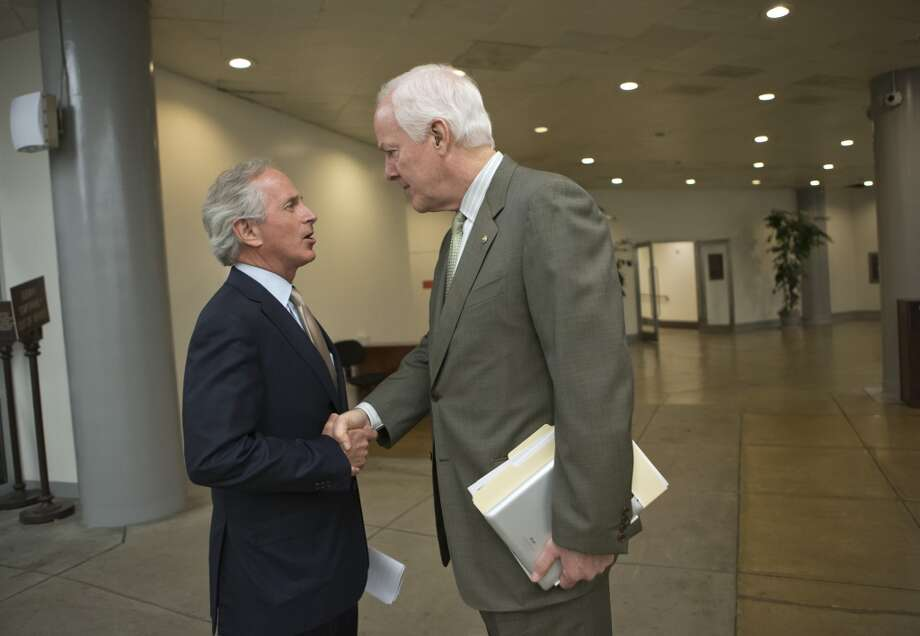 Senate Minority Whip John Cornyn, R-Texas, right, whose border-security amendment to the Gang of Eight's immigration-reform bill was rejected last week, speaks with Sen. Bob Corker, R-Tenn., left, prior to a vote in the Senate on a measure in the immigration reform bill crafted by Corker and Sen. John Hoeven, R-N.D., that includes changes to the original border security provisions in the bill that would double the size of the U.S. Border Patrol and completes 700 miles of fencing on the border with Mexico, at the Capitol in Washington, Monday, June 24, 2013.  (AP Photo/J. Scott Applewhite) Photo: J. Scott Applewhite, Associated Press
