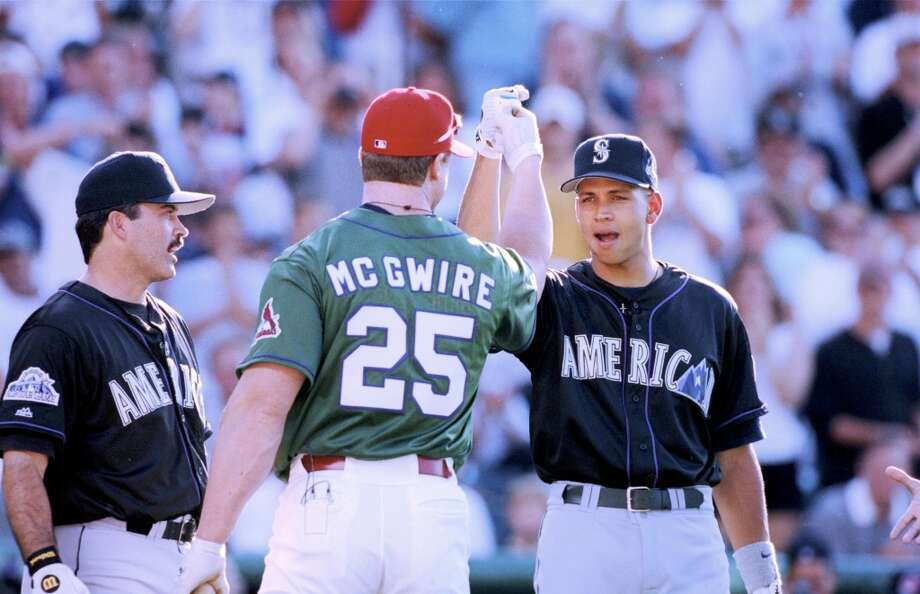 Alex Rodriguez of the American League and Seattle Mariners bumps fists with Mark McGwire #25 of the National League and St. Louis Cardinals as Rafael Palmeiro #25 of the American League and Texas Rangers looks on during the 1998 MLB All-Star Game Home Run Derby at Coors Field on July 6, 1998 in Denver, Colorado. Photo: Brian Bahr, Getty Images / 1998 Getty Images