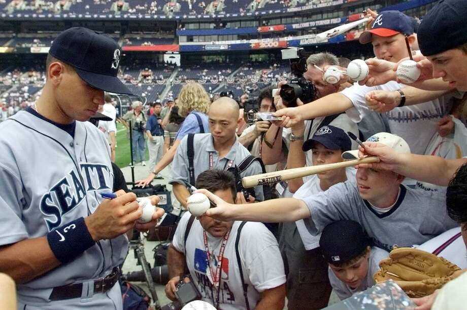 American League All-Star Alex Rodriguez (L) of the Seattle Mariners signs autographs for fans during batting practice 11 July, 2000, for the 2000 All-Star game at Turner Field in Atlanta. Rodriguez was selected as a starter for the game but will not play because of an injury. Photo: Chris Firor, AFP/Getty Images / AFP