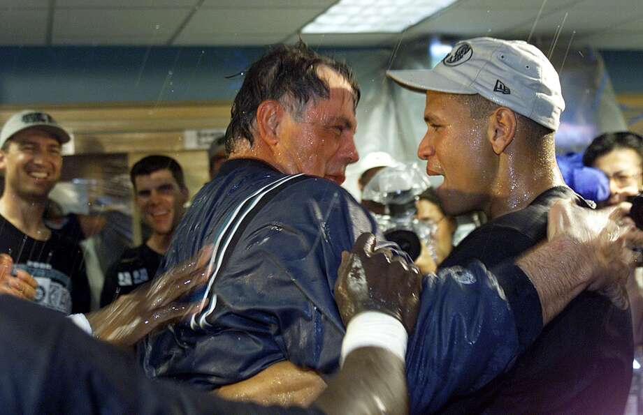 Seattle Mariner Alex Rodriguez (R) embraces manager Lou Piniella (C) in the clubhouse after the team's 5-2 victory over the Anaheim Angels, and their clinching of the AL Wildcard playoff birth  01 October 2000 at Edison Field in Anaheim, CA. AFP Photo Scott Nelson (Photo credit should read Scott Nelson/AFP/Getty Images) Photo: Scott Nelson, AFP/Getty Images / AFP
