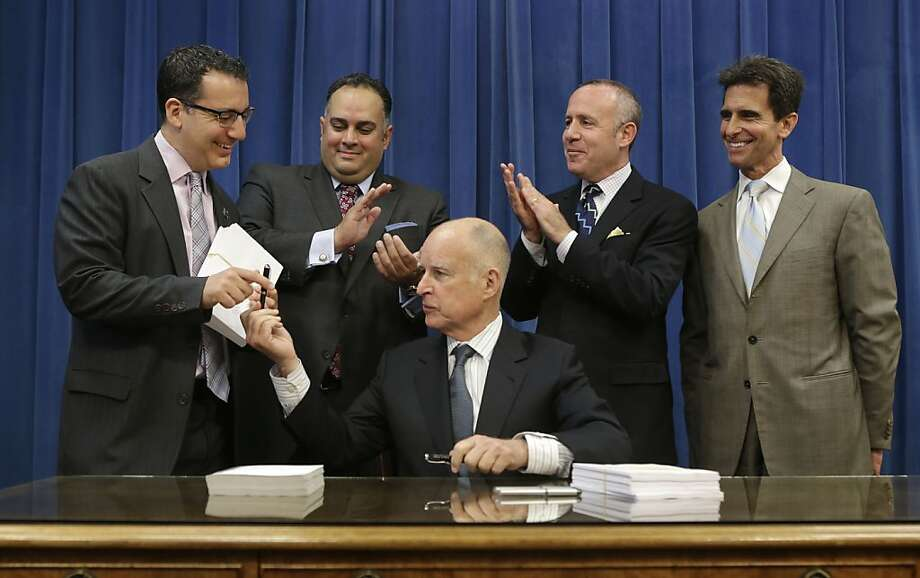 Gov. Jerry Brown hands Assemblyman Bob Blumenfield, D-Woodland Hills (Los Angeles County), the pen with which he signed the new budget. Also attending the signing ceremony are Assembly Speaker John Pérez (left), state Senate President Pro Tem Darrell Steinberg and state Sen. Mark Leno, D-San Francisco. Photo: Rich Pedroncelli, Associated Press