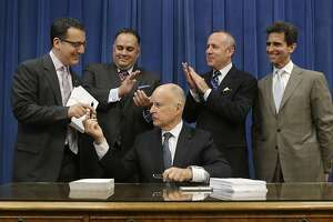 Gov. Jerry Brown hands Assemblyman Bob Blumenfield, D-Woodland Hills, the pen he used to sign one of the copies of the state budget at the Capitol Thursday, June 27, 2013, in Sacramento, Calif.  The $96.3 billion spending plan ends years of deficits, channels more money to school districts with disadvantaged students and restores millions of dollars to social service programs cut during the recession.  Also seen, from left, are Assembly Speaker John Perez,D-Los Angeles,  Senate President Pro Tem Darrell Steinberg, D-Sacramento, and Sen. Mark Leno, D-San Francisco, chairman of the Senate budget committee, right.(AP Photo/Rich Pedroncelli)