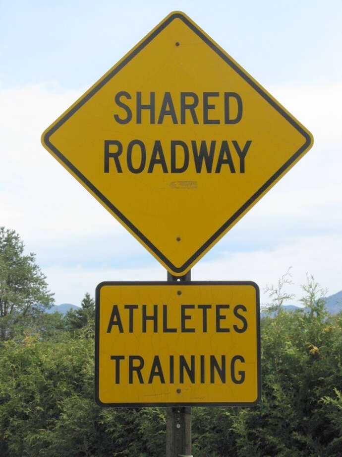 A road sign outside the village of Lake Placid in the Adirondacks warns drivers they'll be sharing the road with runners and cyclists. (Gillian Scott/Times Union) Photo: Picasa 2.7