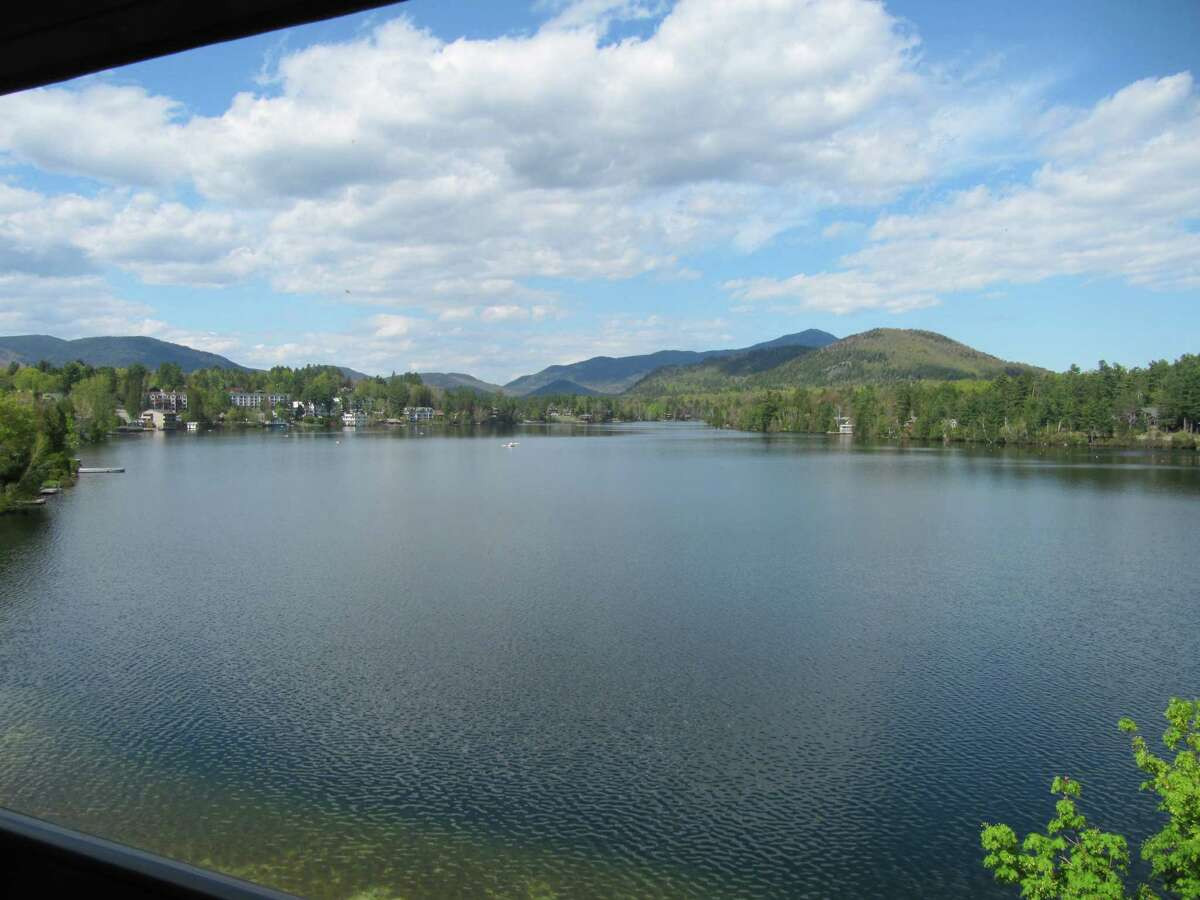 The mountains of the Adirondack High Peaks region are visible across the water of Mirror Lake in the village of Lake Placid. (Gillian Scott/Times Union)