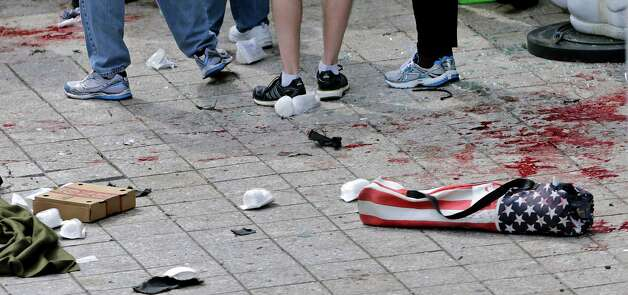 FILE - In this April 15, 2013, file photo, blood from victims covers the sidewalk on Boylston Street, at the site of an explosion during the 2013 Boston Marathon in Boston. At right foreground is a folding chair with the design of an American flag on the cover. A federal grand jury in Boston returned a 30-count indictment against bombing suspect Dzhokhar Tsarnaev on Thursday, June 27, 2013, on charges including using a weapon of mass destruction and bombing a place of public use, resulting in death. Photo: Charles Krupa