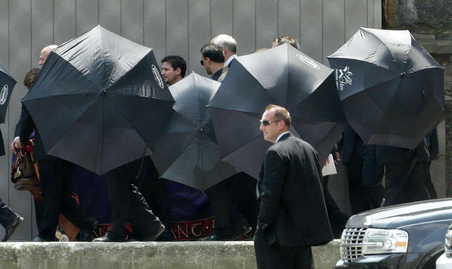 "Men hold umbrellas as pallbearers walk with a casket containing the body of actor James Gandolfini at Cathedral Church of Saint John the Divine after funeral services for Gandolfini, Thursday, June 27, 2013, in New York. Gandolfini, who played Tony Soprano in the HBO show ""The Sopranos"", died while vacationing in Italy last week. Photo: Julio Cortez, Associated Press / AP"