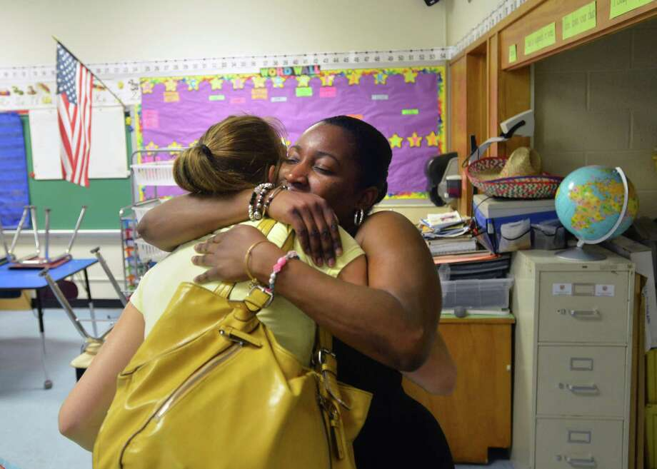 At right, Lisa Moore, a New Lebanon School second-grade teacher, hugs New Lebanon School first-grade teacher, Elaina Weaver, on the last day of the school year for staff in the Greenwich school district, Thursday, June 27, 2013. Weaver said that she is leaving the school after eight years as a first-grade teacher but will be staying in Greenwich continuing as an elementary school teacher at North Minaus School when the new school year begins on August 27. Photo: Bob Luckey / Greenwich Time