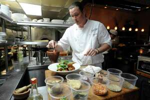 Chef Jason Dady puts a garnish over his Thai red curry wings at Bin 555 on Tuesday, May 14, 2013.