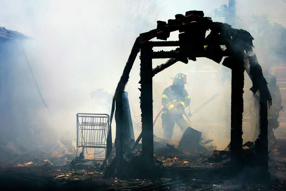 Firefighters work to put out a blaze that started in a small business complex at the corner of E Hardy, and Warwick Roads, Thursday, June 27, 2013, in Houston. Photo: Cody Duty, Houston Chronicle / © 2013 Houston Chronicle