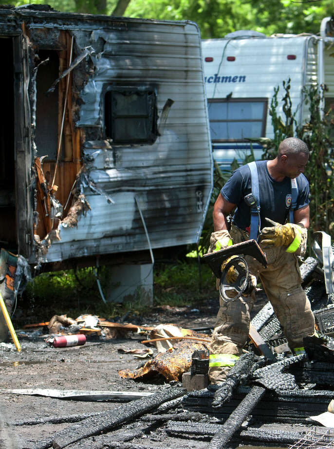 Firefighters look for hot spots after a fire started in a small business complex at the corner of E Hardy, and Warwick Roads, Thursday, June 27, 2013, in Houston. Photo: Cody Duty, Houston Chronicle / © 2013 Houston Chronicle