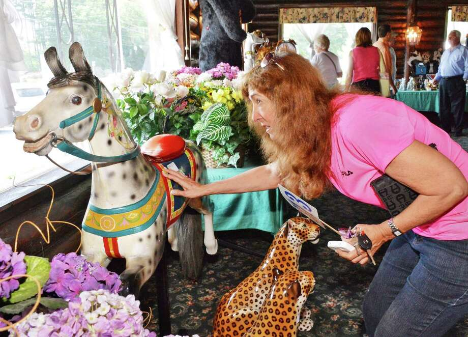 Faith Fehr of Lake George takes a close look at a carousel horse at the former Montcalm restaurant in Lake George, NY, during an auction of items from nearly 60 years in business Thursday June 27, 2013.  The landmark business will be replaced by an outlet mall.  (John Carl D'Annibale / Times Union) Photo: John Carl D'Annibale / 00022975A