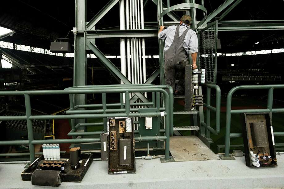 Jeff Fleck scales a ladder to wire up pyrotechnic charges near the top of Safeco Field for a first-ever Mariners post-game fireworks show Thursday, June 27, 2013, in Seattle. Between 1,200-1,500 charges will be set up for Friday's 15 minute display set to music. The program will still take place even if there is light rain. Lighting, thunder, heavy rain and high winds would prompt cancellation of the show. Photo: JORDAN STEAD, SEATTLEPI.COM / SEATTLEPI.COM
