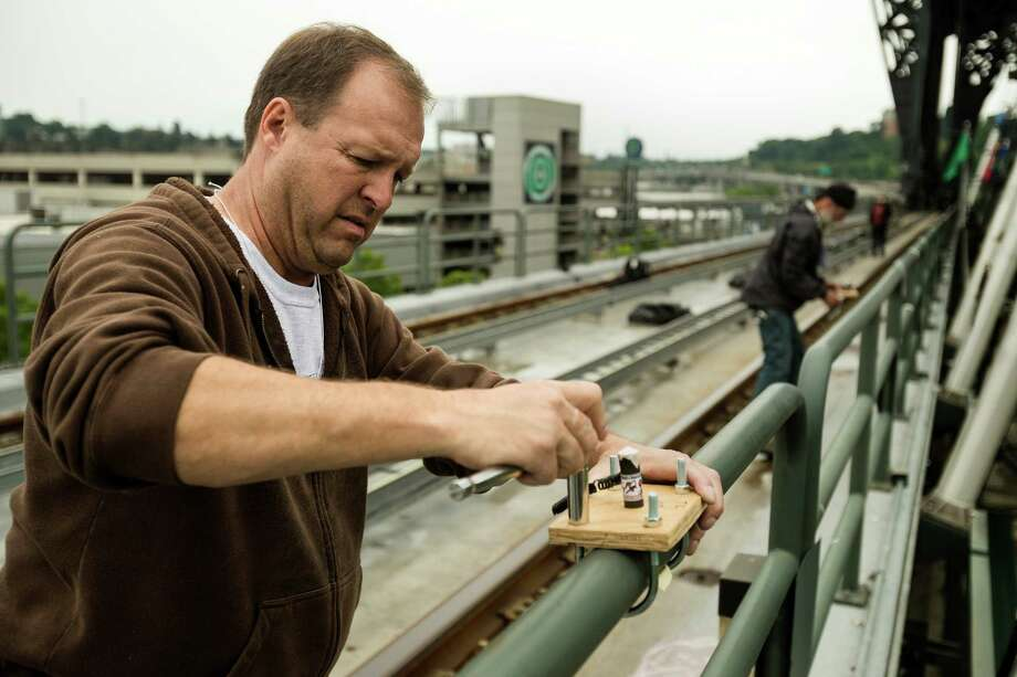 John Bouman helps to wire and place pyrotechnic charges for a first-ever Mariners post-game fireworks show Thursday, June 27, 2013, at Safeco Field in Seattle. Between 1,200-1,500 charges will be set up for Friday's 15 minute display set to music. The program will still take place even if there is light rain. Lighting, thunder, heavy rain and high winds would prompt cancellation of the show. Photo: JORDAN STEAD, SEATTLEPI.COM / SEATTLEPI.COM