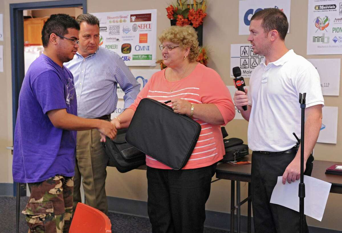 From left, Jacobo Malulan, 18, of Cohoes shakes hands with Wil Hebert, Chairman of Cohoes Housing Authority, Sandra Beston, Chairperson of the Watervliet Housing Authority, and Matt Ethier, public housing program coordinator for Watervilet Housing Authority, as he recieves his free laptop for college at the Dr. Jay McDonald Towers on Thursday, June 27, 2013 in Cohoes, N.Y. The Cohoes and Watervliet housing authorities gave away free laptops to 11 college-bound graduating seniors of the Cohoes and Watervliet city school districts and Green Island Union Free School District. (Lori Van Buren / Times Union)