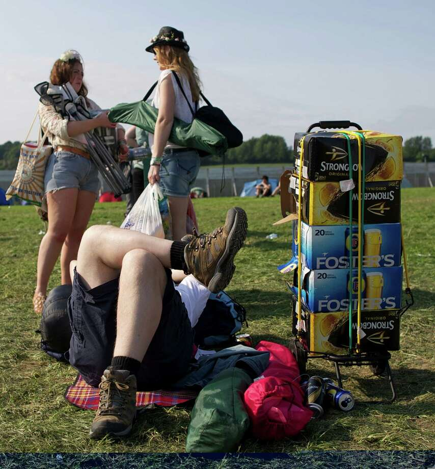 Festivalgoers relax in the evening sunshine on the first day of the Glastonbury Festival of Contemporary Performing Arts near Glastonbury, southwest England on June 26, 2013. The festival attracts 170,000 party-goers to the dairy farm in Somerset, and this year's tickets sold out within two hours of going on sale. The Rolling Stones will perform at the festival for the first time, headlining on Saturday night. Photo: ANDREW COWIE, AFP/Getty Images / AFP