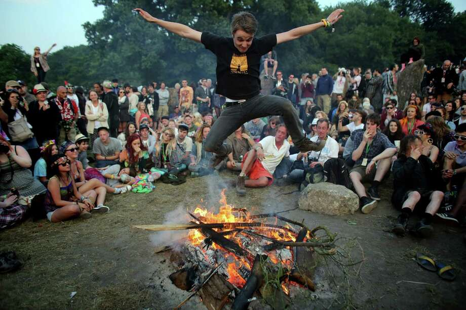 A man jumps over a fire that has been lit inside the stone circle as people gather for sunset at the Glastonbury Festival of Contemporary Performing Arts site at Worthy Farm, Pilton on June 26, 2013 near Glastonbury, England.  Gates opened on Wednesday at the Somerset diary farm that will be playing host to one of the largest music festivals in the world and this year features headline acts Artic Monkeys, Mumford and Sons and the Rolling Stones. Tickets to the event which is now in its 43rd year sold out in minutes and that was before any of the headline acts had been confirmed. The festival, which started in 1970 when several hundred hippies paid 1 GBP to watch Marc Bolan, now attracts more than 175,000 people over five days. Photo: Matt Cardy, Getty Images / 2013 Getty Images