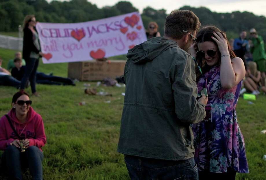 A man proposes to his girlfriend with a large banner on the first day of the Glastonbury Festival of Contemporary Performing Arts near Glastonbury, southwest England on June 26, 2013. The festival attracts 170,000 party-goers to the dairy farm in Somerset, and this year's tickets sold out within two hours of going on sale. The Rolling Stones will perform at the festival for the first time, headlining on Saturday night. Photo: ANDREW COWIE, AFP/Getty Images / AFP