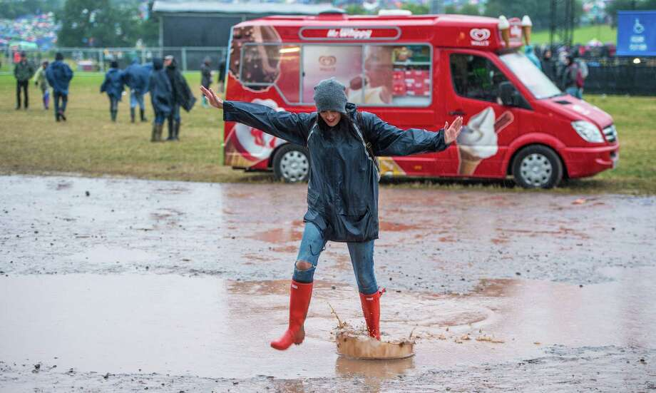 A festival goer jumps through a puddle as rain falls during day 1 of the 2013 Glastonbury Festival at Worthy Farm on June 27, 2013 in Glastonbury, England. Photo: Ian Gavan, Getty Images / 2013 Getty Images
