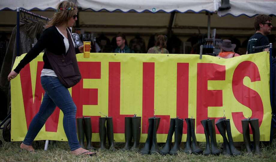 A festival goer walks past a stall selling rubber boots on the second day of the Glastonbury Festival of Contemporary Performing Arts near Glastonbury, southwest England on June 27, 2013. The festival attracts 170,000 party-goers to the dairy farm in Somerset, and this year's tickets sold out within two hours of going on sale. The Rolling Stones will perform at the festival for the first time, headlining on Saturday night. Photo: ANDREW COWIE, AFP/Getty Images / AFP