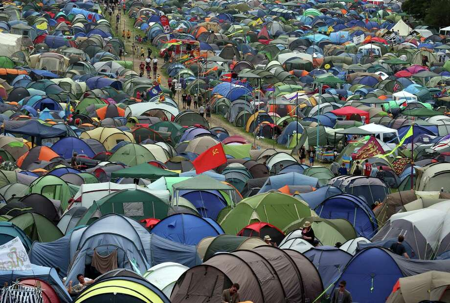 People walk past tents at the Glastonbury Festival of Contemporary Performing Arts site at Worthy Farm, Pilton on June 27, 2013 near Glastonbury, England. Gates opened on Wednesday at the Somerset Diary Farm that will be playing host to one of the largest music festivals in the world and this year features headline acts Artic Monkeys, Mumford and Sons and the Rolling Stones. Tickets to the event which is now in its 43rd year sold out in minutes and that was before any of the headline acts had been confirmed. The festival, which started in 1970 when several hundred hippies paid 1 GBP to watch Marc Bolan, now attracts more than 175,000 people over five days. Photo: Matt Cardy, Getty Images / 2013 Getty Images