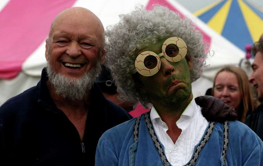 Festival founder Michael Eavis (L) poses for a photograph with a performer at the Glastonbury Festival of Contemporary Performing Arts site at Worthy Farm, Pilton on June 27, 2013 near Glastonbury, England. Gates opened on Wednesday at the Somerset Diary Farm that will be playing host to one of the largest music festivals in the world and this year features headline acts Artic Monkeys, Mumford and Sons and the Rolling Stones. Tickets to the event which is now in its 43rd year sold out in minutes and that was before any of the headline acts had been confirmed. The festival, which started in 1970 when several hundred hippies paid 1 GBP to watch Marc Bolan, now attracts more than 175,000 people over five days. Photo: Matt Cardy, Getty Images / 2013 Getty Images