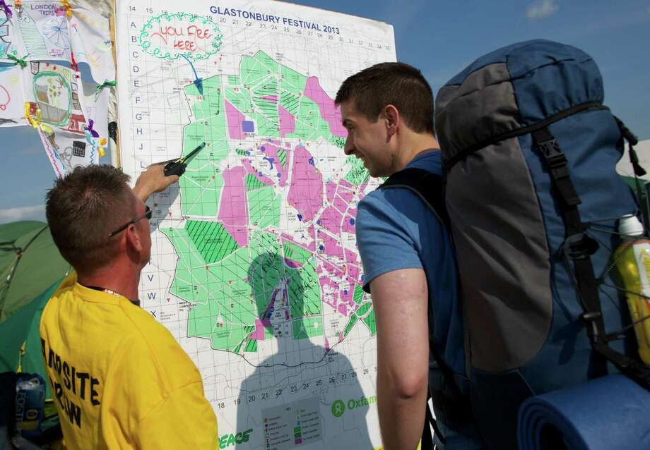 A festivalgoer studies a map of the site after arriving on the first day of the Glastonbury Festival of Contemporary Performing Arts near Glastonbury, southwest England on June 26, 2013. The festival attracts 170,000 party-goers to the dairy farm in Somerset, and this year's tickets sold out within two hours of going on sale. The Rolling Stones will perform at the festival for the first time, headlining on Saturday night. Photo: ANDREW COWIE, AFP/Getty Images / AFP