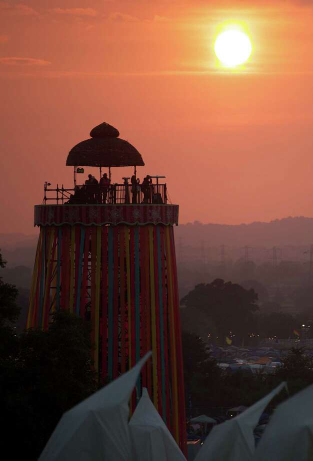Festivalgoers look out from a viewing tower as the sun sets on the first day of the Glastonbury Festival of Contemporary Performing Arts near Glastonbury, southwest England on June 26, 2013. The festival attracts 170,000 party-goers to the dairy farm in Somerset, and this year's tickets sold out within two hours of going on sale. The Rolling Stones will perform at the festival for the first time, headlining on Saturday night. Photo: ANDREW COWIE, AFP/Getty Images / AFP