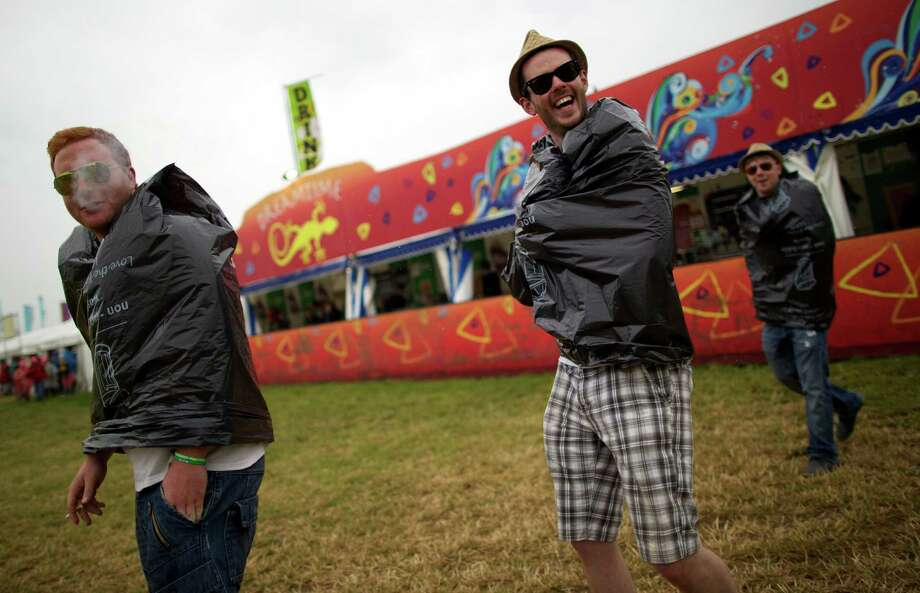 Festival goers walk around the site on the second day of the Glastonbury Festival of Contemporary Performing Arts near Glastonbury, southwest England, on June 27, 2013. The festival attracts 170,000 party-goers to the dairy farm in Somerset, and this year's tickets sold out within two hours of going on sale. The Rolling Stones will perform at the festival for the first time, headlining on Saturday night. Photo: ANDREW COWIE, AFP/Getty Images / AFP