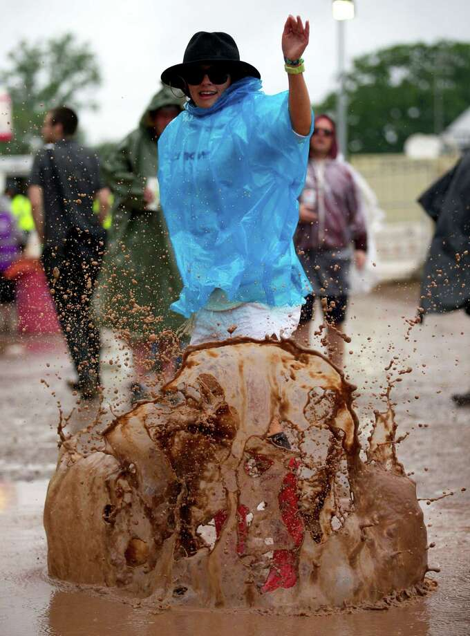 A festival goer jumps in a mud puddle on the second day of the Glastonbury Festival of Contemporary Performing Arts near Glastonbury, southwest England, on June 27, 2013. The festival attracts 170,000 party-goers to the dairy farm in Somerset, and this year's tickets sold out within two hours of going on sale. The Rolling Stones will perform at the festival for the first time, headlining on Saturday night. Photo: ANDREW COWIE, AFP/Getty Images / AFP