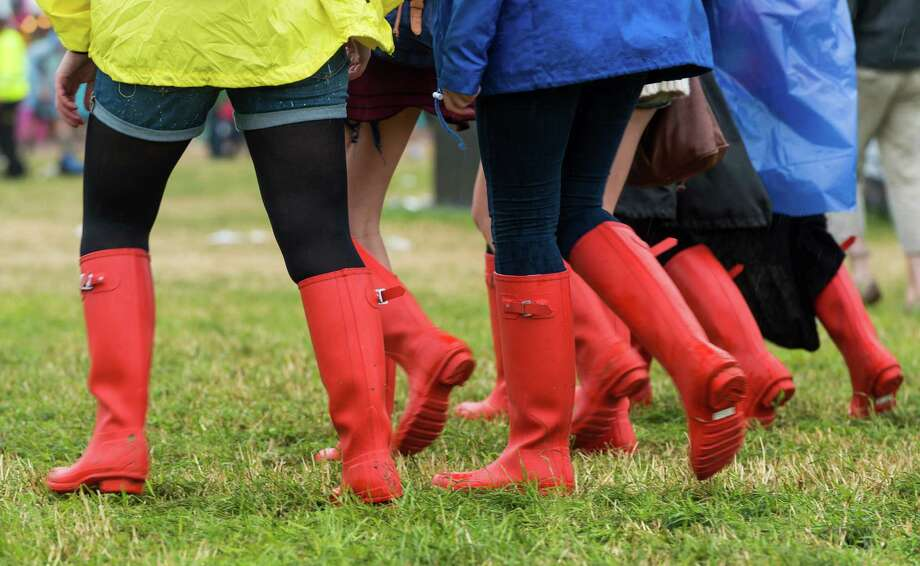 Festival goers enjoy the atmosphere as rain falls during day 1 of the 2013 Glastonbury Festival at Worthy Farm on June 27, 2013 in Glastonbury, England. Photo: Ian Gavan, Getty Images / 2013 Getty Images