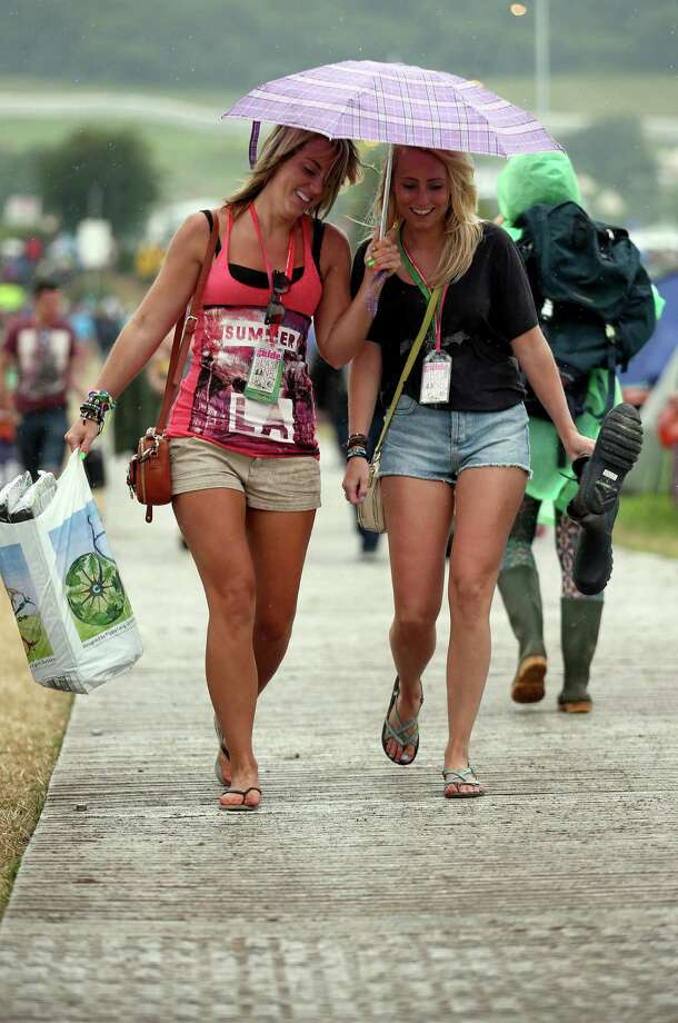Festival goers walk in the rain at the Glastonbury Festival of Contemporary Performing Arts site at Worthy Farm, Pilton on June 27, 2013 near Glastonbury, England. Gates opened on Wednesday at the Somerset Diary Farm that will be playing host to one of the largest music festivals in the world and this year features headline acts Artic Monkeys, Mumford and Sons and the Rolling Stones. Tickets to the event which is now in its 43rd year sold out in minutes and that was before any of the headline acts had been confirmed. The festival, which started in 1970 when several hundred hippies paid 1 GBP to watch Marc Bolan, now attracts more than 175,000 people over five days. Photo: Matt Cardy, Getty Images / 2013 Getty Images