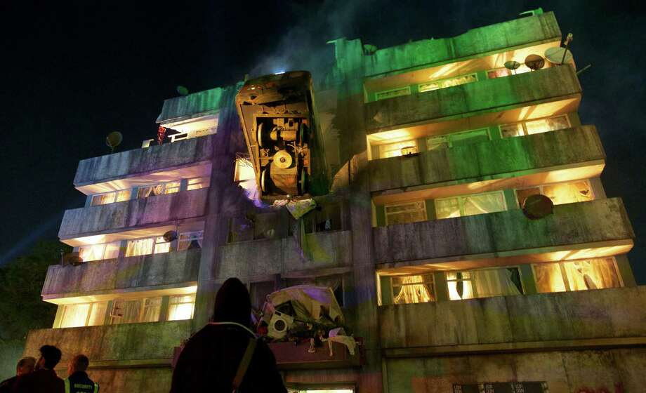 TOPSHOTS People look at the exterior of a bar made in the form of a block of flats with a London Underground train crashed into it on the first night of the Glastonbury Festival of Contemporary Performing Arts near Glastonbury, southwest England late on June 26, 2013.  The festival attracts 170,000 party-goers to the dairy farm in Somerset, and this year's tickets sold out within two hours of going on sale. The Rolling Stones will perform at the festival for the first time, headlining on Saturday night. Photo: ANDREW COWIE, AFP/Getty Images / AFP