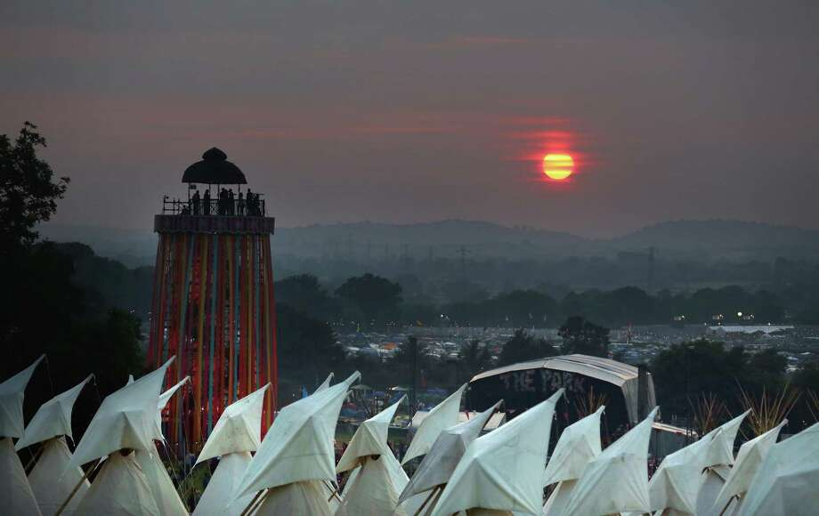 The sun begins to set over tipis at the Glastonbury Festival of Contemporary Performing Arts site at Worthy Farm, Pilton on June 26, 2013 near Glastonbury, England.  Gates opened on Wednesday at the Somerset diary farm that will be playing host to one of the largest music festivals in the world and this year features headline acts Artic Monkeys, Mumford and Sons and the Rolling Stones. Tickets to the event which is now in its 43rd year sold out in minutes and that was before any of the headline acts had been confirmed. The festival, which started in 1970 when several hundred hippies paid 1 GBP to watch Marc Bolan, now attracts more than 175,000 people over five days. Photo: Matt Cardy, Getty Images / 2013 Getty Images