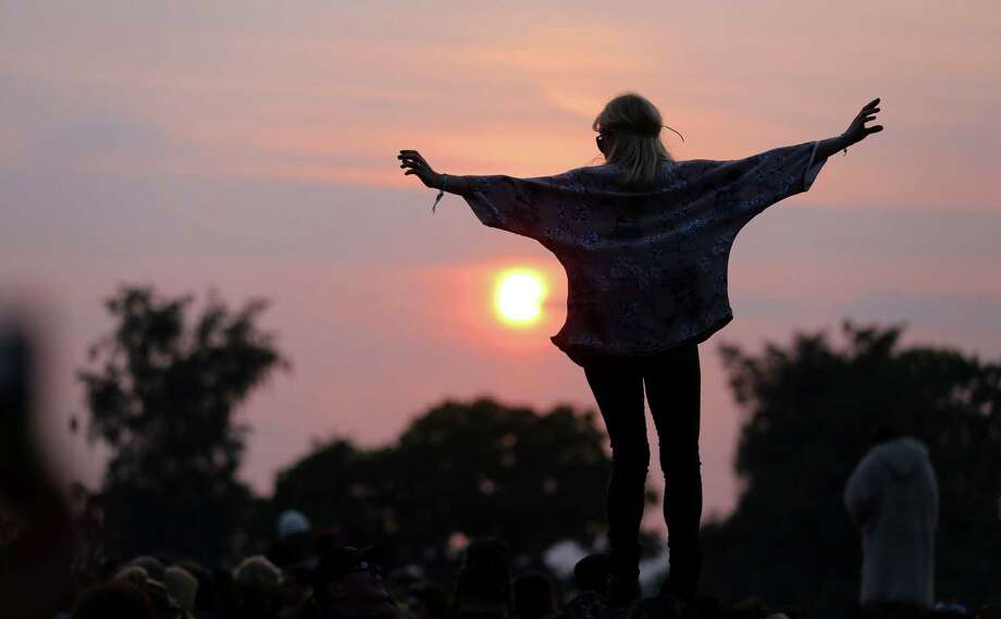 A woman stands on a rock at the stone circle as people gather for sunset at the Glastonbury Festival of Contemporary Performing Arts site at Worthy Farm, Pilton on June 26, 2013 near Glastonbury, England.  Gates opened on Wednesday at the Somerset diary farm that will be playing host to one of the largest music festivals in the world and this year features headline acts Artic Monkeys, Mumford and Sons and the Rolling Stones. Tickets to the event which is now in its 43rd year sold out in minutes and that was before any of the headline acts had been confirmed. The festival, which started in 1970 when several hundred hippies paid 1 GBP to watch Marc Bolan, now attracts more than 175,000 people over five days. Photo: Matt Cardy, Getty Images / 2013 Getty Images