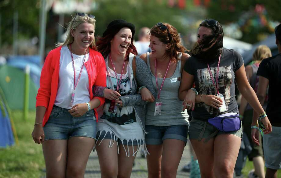 Gemma Wigmore, Emily Golding, Leanne Scull and Charlotte Wigmore, all from Bristol laugh as they walk around the Glastonbury Festival of Contemporary Performing Arts site at Worthy Farm, Pilton on June 26, 2013 near Glastonbury, England. Gates opened today at the Somerset diary farm that will be playing host to one of the largest music festivals in the world and this year features headline acts Artic Monkeys, Mumford and Sons and the Rolling Stones. Tickets to the event which is now in its 43rd year sold out in minutes and that was before any of the headline acts had been confirmed. The festival, which started in 1970 when several hundred hippies paid 1 GBP to watch Marc Bolan, now attracts more than 175,000 people over five days. Photo: Matt Cardy, Getty Images / 2013 Getty Images