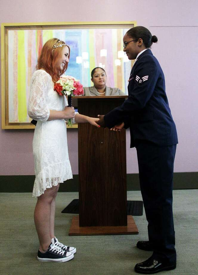 NEW YORK, NY - JUNE 27:  U.S. Air Force Senior Airman Shyla Smith (R) and Courtney Burdeshaw hold hands in the west chapel during their wedding ceremony at the Manhattan Marriage Bureau the day after the U.S. Supreme Court ruling on DOMA on June 27, 2013 in New York City. The high court struck down the Defense of Marriage Act (DOMA) and ruled that supporters of California's ban on gay marriage, Proposition 8, could not defend it before the Supreme Court.  The pair said they planned to get married today before the ruling came down.  (Photo by Mario Tama/Getty Images) ORG XMIT: 171882356 Photo: Mario Tama / 2013 Getty Images