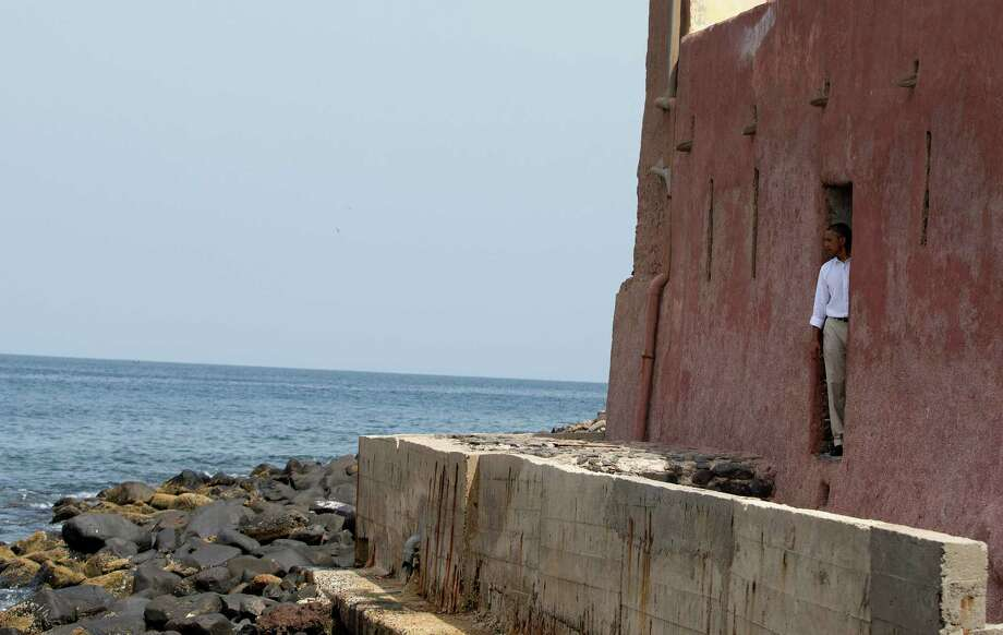 "President Barack Obama looks out of the ""door of no return"" during a tour of Goree Island, Thursday, June 27, 2013, in Goree Island, Senegal. Goree Island is the site of the former slave house and embarkation point built by the Dutch in 1776, from which slaves were brought to the Americas. The ""door of no return"" was the entrance to the slave ships. (AP Photo/Evan Vucci) ORG XMIT: SENV205 Photo: Evan Vucci / AP"