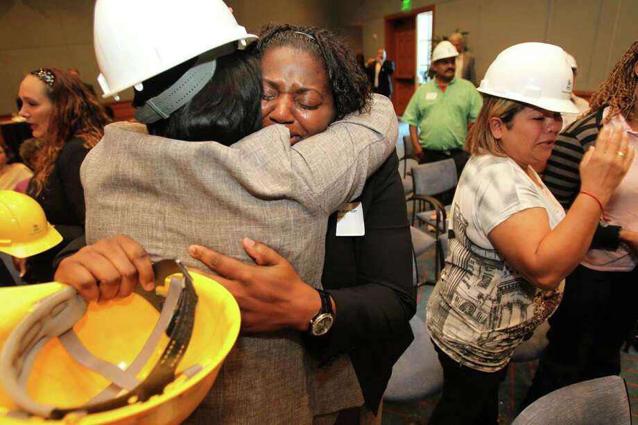 Geraldine Johnson embraces Gloria Tucker they react to a surprise announcement that they were selected for a Habitat for Humanity home during a reception at the Federal Reserve Bank on Thursday, June 27, 2013, in Houston. The successful 37 families selected were chosen from a pool of 165 applicants. Photo: Mayra Beltran / © 2013 Houston Chronicle